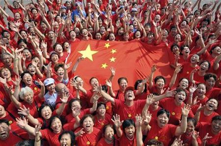 People hold a Chinese national flag ahead of a raising-flag ceremony during a photo call at Yangren Street in Chongqing Municipality, September 29, 2009