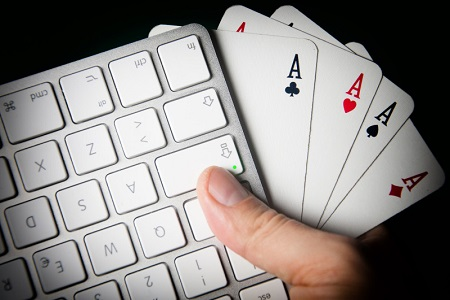 A keyboard and four aces in hand.